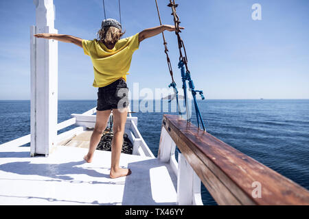 Indonesia, Komodo National Park, girl on a sailing boat - Stock Photo