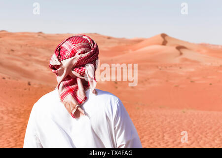 Bedouin in National dress standing in the desert, rear view, Wahiba Sands, Oman - Stock Photo