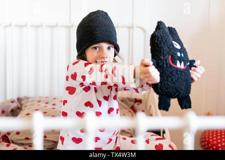 Portrait of little girl wearing cap sitting in bed with her soft toy - Stock Photo