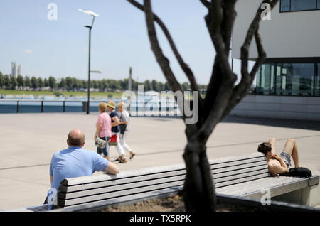 24 June 2019, North Rhine-Westphalia, Cologne: Two people from Cologne enjoy their lunch break outside in the Rheinauhafen harbour. Photo: Oliver Berg/dpa - Stock Photo