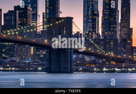 The Brooklyn Bridge over the East River at sunset, New York, USA - Stock Photo