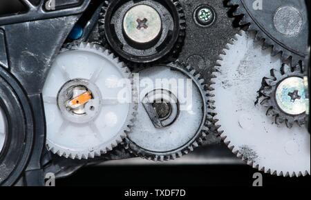 Close up view of ink-stained plastic cog wheels and screws and other components from a printer cartridge. - Stock Photo
