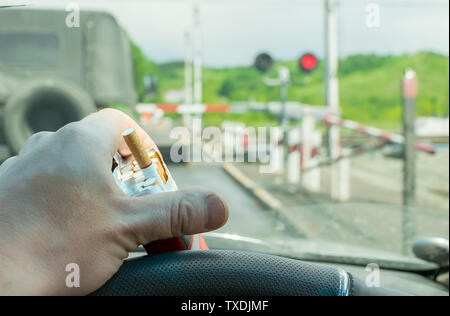 View of the driver hand with a pack of cigarettes on the steering wheel of the car, which stopped before a closed railway crossing at a red light - Stock Photo