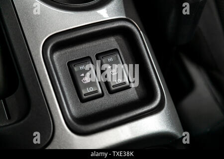 Close-up on the seat heatting buttons. modern car interior: parts, buttons, knobs - Stock Photo