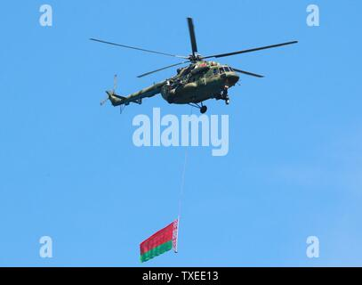 Minsk, Belarus. 24th June, 2019. A helicopter carries a national flag during a rehearsal for the military parade marking the Independence Day of Belarus in Minsk, Belarus, June 24, 2019. The military parade marking the Independence Day of Belarus will kick off on July 3. Credit: Efim Mazurevich/Xinhua/Alamy Live News - Stock Photo