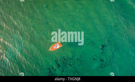Aerial drone view of beautiful clean waters in Corfu Greece and an isolated orange boat.Copy space - Stock Photo