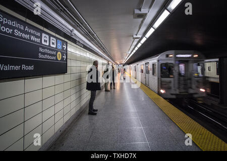 TORONTO, CANADA - NOVEMBER 14, 2018: People waiting for a subway in Spadina station platform, while a metro train operated by TTC, Toronto Transit Com - Stock Photo