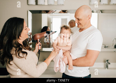 Mother and father drying baby daughter's hair in bathroom - Stock Photo
