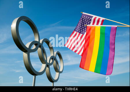 LONDON - MAY 4, 2019: A rainbow colored gay pride flag hangs together with an American flag in front of Olympic Rings against bright blue sky. - Stock Photo