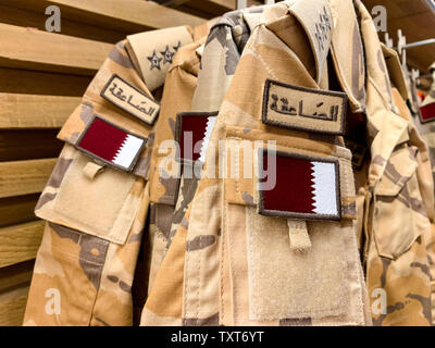Military pattern workwear with the Qatari flag hanging in a row. April 2019, Doha/ Qatar. - Stock Photo
