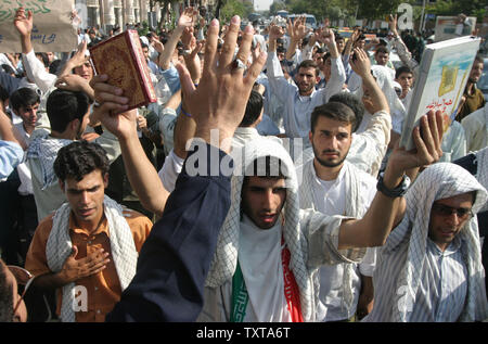 Iranian students chant slogans and hold the Muslims holy book, the Quran, left, and a Shiites' holy book during a demonstration in front of the British Embassy in Tehran, August 14, 2005.(UPI photo/Mohammad Kheirkhah) - Stock Photo