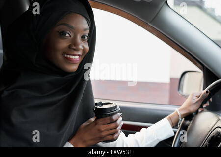 Positive, cheerful african girl sitting in car posing, holding hand on steering wheel. Beautiful muslim woman wearing in black hijab with perfect smile looking at camera, holding coffee cup. - Stock Photo