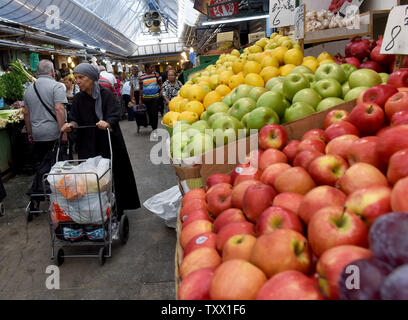 An Orthodox Jewish woman shops in the Mahane Yehuda Market in Jerusalem, Israel,  September 5, 2018, in preparation for Rosh HaShana, the Jewish New Year, which starts at sundown on Sunday, September 9, 2018. Pomegranates, apples and honey are traditionally eaten during the Jewish High holidays which is the period of repentance in the Jewish calendar. The abundance of seeds in the pomegranate is associated with the 613 commandments in the Torah and serve as symbols of righteousness and fruitfulness.  Photo by Debbie Hill/UPI - Stock Photo