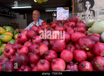 An Israeli sells pomegranates in the Mahane Yehuda Market in Jerusalem, Israel,  September 5, 2018, for Rosh HaShana, the Jewish New Year, which starts at sundown on Sunday, September 9, 2018. Pomegranates, apples and honey are traditionally eaten during the Jewish High holidays which is the period of repentance in the Jewish calendar. The abundance of seeds in the pomegranate is associated with the 613 commandments in the Torah and serve as symbols of righteousness and fruitfulness.  Photo by Debbie Hill/UPI - Stock Photo