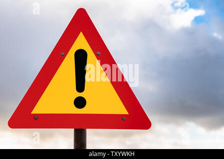 Hazard ahead warning road sign against cloudy sky - Stock Photo