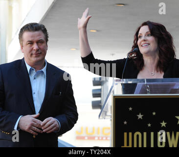 Actor Alec Baldwin listens as actress Megan Mullally makes comments during an unveiling ceremony honoring him with the 2,433rd star on the Hollywood Walk of Fame in Los Angeles on February 14, 2011.  UPI/Jim Ruymen - Stock Photo