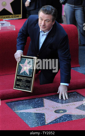 Actor Alec Baldwin holds a replica plaques as he touches his star during an unveiling ceremony honoring him with the 2,433rd star on the Hollywood Walk of Fame in Los Angeles on February 14, 2011.  UPI/Jim Ruymen - Stock Photo