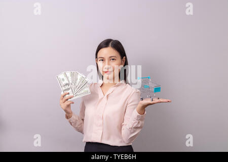 retail commercial business concept, Asian beautiful woman holding banknote money in hand and shopping cart in another hand isolated on grey background - Stock Photo