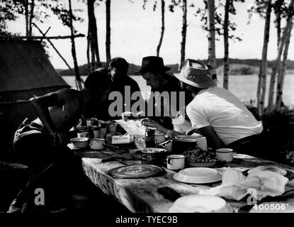Photograph of Two Forest Officers; Scope and content:  Original caption: Two forest officers (Bill Trygg and Merle Moltrup) visit three vacationists camping at a canoe camp site on Birch Point on the south arm of Knife Lake. - Stock Photo