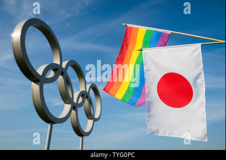 LONDON - MAY 4, 2019: A rainbow colored gay pride flag hangs together with a Japanese flag in front of Olympic Rings against bright blue sky. - Stock Photo