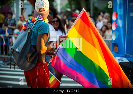 NEW YORK CITY - JUNE 25, 2017: A participant waves a rainbow flag in the annual Gay Pride Parade as it passes through Greenwich Village. - Stock Photo
