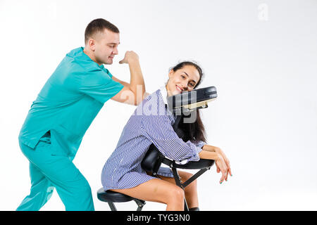 Theme massage and office. Male therapist with blue suit doing back and neck massage for young woman worker, business woman in shirt on massage chair s - Stock Photo