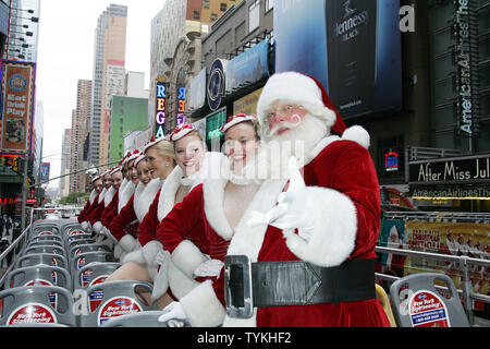 Santa Claus joins the Radio City Rockettes and their wax figure (3rd from right) on top of a double decker bus outside of Madame Tussauds in New York on November 24, 2009.       UPI /Laura Cavanaugh - Stock Photo