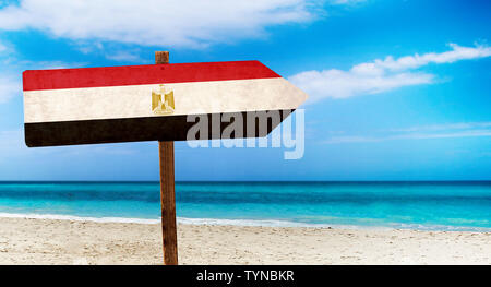 Egypt flag on wooden table sign on beach background. There is beach and clear water of sea and blue sky in the background. - Stock Photo