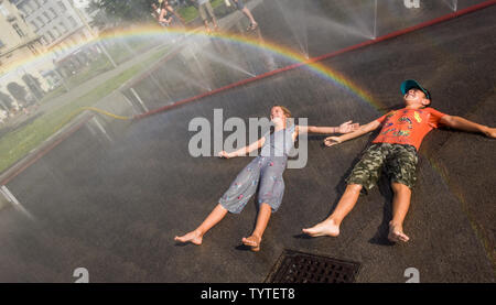 Vienna, Austria. 26th June, 2019. Children cool off at the water spray on the Schwarzenberg Square in Vienna, Austria, on June 26, 2019. The highest temperature in Vienna reached 36 degrees Celsius on Wednesday. The current June is set to be the hottest in recorded history in Austria, with regional heat records also expected to be eclipsed in some parts of the country this week, according to the Central Institute for Meteorology and Geodynamics (ZAMG). Credit: Guo Chen/Xinhua/Alamy Live News - Stock Photo
