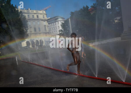 Vienna, Austria. 26th June, 2019. A boy plays at the water spray on the Schwarzenberg Square in Vienna, Austria, on June 26, 2019. The highest temperature in Vienna reached 36 degrees Celsius on Wednesday. The current June is set to be the hottest in recorded history in Austria, with regional heat records also expected to be eclipsed in some parts of the country this week, according to the Central Institute for Meteorology and Geodynamics (ZAMG). Credit: Guo Chen/Xinhua/Alamy Live News - Stock Photo