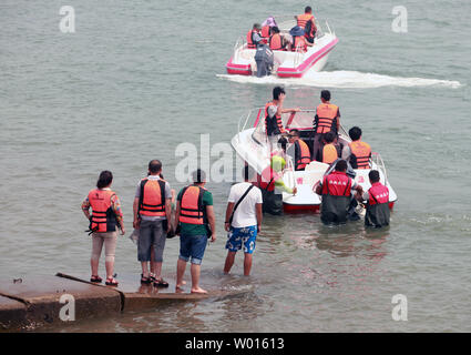 Chinese tourists pay to ride speed boats near the shore of the coastal city Qingdao, a major port in eastern Shandong Province, on August 19, 2014.  China aims to double domestic spending on tourism by 2020 by offering financial support to develop the growing sector, according to the government, as it seeks to boost spending at home to spur economic growth.    UPI/Stephen Shaver - Stock Photo