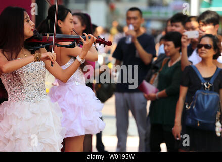 Chinese musicians hired by a jewelry chain play electric violins in hopes of attracting customers to the shop in Beijing on September 15, 2015.  Economic experts remain worried by turmoil in China's stock markets, and signs that the country's massive economy is flagging.   Photo by Stephen Shaver/UPI - Stock Photo
