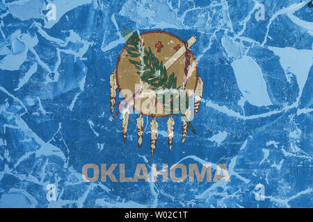 The national flag of the US state Oklahoma in against a gray wall with cracks and faults on the day of independence in colors of blue and yellow. Poli - Stock Photo