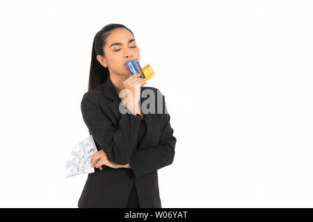 Beautiful Asian business woman wearing a black suit, right hand holding a blue and yellow credit card, , kissing a credit card at the mouth, left hand - Stock Photo