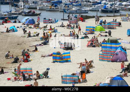 Lyme Regis, Dorset, UK.  27th June 2019. UK Weather.  Sunbathers flock to the beach at the seaside resort of Lyme Regis in Dorset to enjoy a day of clear blue skies and scorching sunshine.   Picture Credit: Graham Hunt/Alamy Live News - Stock Photo