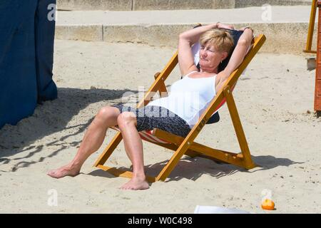 Lyme Regis, Dorset, UK.  27th June 2019. UK Weather.  A woman sunbathing at the seaside resort of Lyme Regis in Dorset as they enjoy a day of clear blue skies and scorching sunshine.   Picture Credit: Graham Hunt/Alamy Live News - Stock Photo