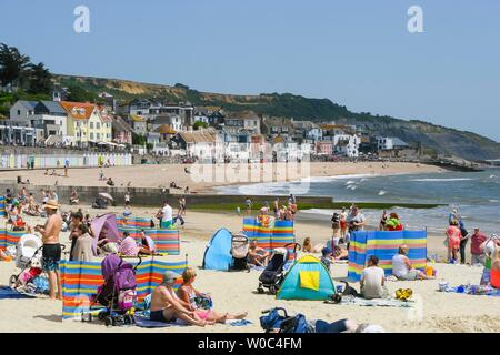 Lyme Regis, Dorset, UK.  27th June 2019. UK Weather.  Sunbathers on the beach at the seaside resort of Lyme Regis in Dorset enjoying a day of clear blue skies and scorching sunshine.   Picture Credit: Graham Hunt/Alamy Live News - Stock Photo