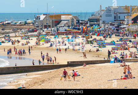 Lyme Regis, Dorset, UK. 27th June 2019. UK Weather: Sunseekers flock to the picturesque seaside resort of Lyme Regis to soak up the scorching hot sunshine and bright blue skies as the Saharan heatwave hits the UK. Visitors and locals bask in sweltering sun on the town's sandy beach. Credit: Celia McMahon/Alamy Live News. - Stock Photo