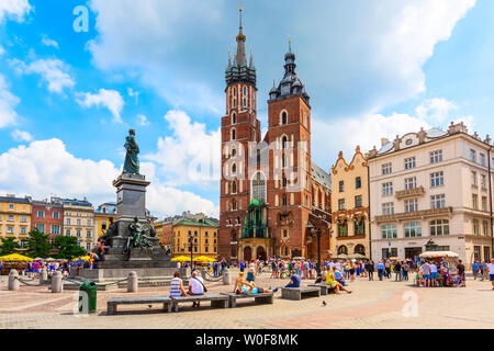 Krakow, Poland - June 18, 2019: Panoramic day view of main market square Rynek Glowny with St Mary Basilica - Stock Photo