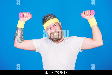 Sportsman training with dumbbells blue background. Improve your muscles. Use weights or dumbbells. Man bearded athlete exercising dumbbell. Athlete training with tiny dumbbell. Motivated athlete guy. - Stock Photo