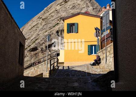 PIETRAPERTOSA, ITALY - NOVEMBER 13, 2018: Old man takes a rest under the sun at the corner of an alley in the old centre of Pietrapertosa village. - Stock Photo