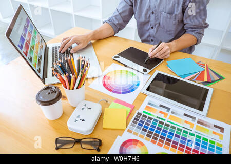Young creative graphic designer working on project architectural drawing and color swatches, selection coloring on graphic chart with work tools and e - Stock Photo