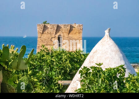 Baroque watchtower, beautiful old tower in San Vito, Polignano a Mare, Bari, Puglia, Italy with blue sea, boat,, cactus, fig trees and trullo, Mediter - Stock Photo