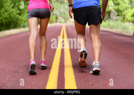 Running people. Runners jogging close up of sport fitness running shoes and legs and shorts. Athletes, woman and man in outdoor workout training for health and fitness. - Stock Photo