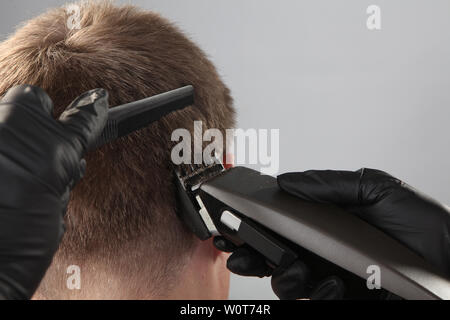 comb and clipper in the hands of a hairdresser - Stock Photo