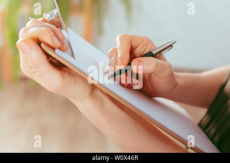 caucasian woman's hands holds clipboard - Stock Photo