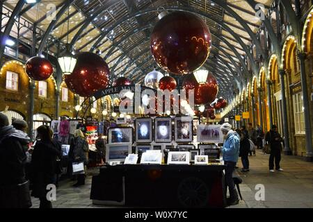 London/UK - November 27, 2013: People shopping at the Covent Garden Apple market decorated for Christmas holidays. - Stock Photo