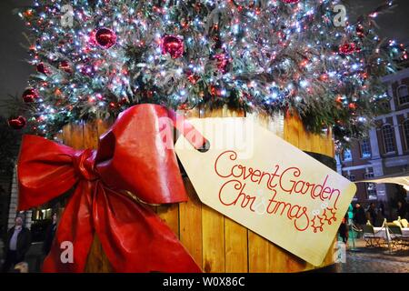 London/UK - November 27, 2013: Close-up view to traditional Christmas tree of the Covent Garden square  in a wooden barrel decorated with red bow. - Stock Photo