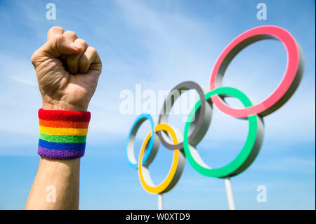 LONDON - MAY 4, 2019: A hand wearing LGBTQI pride rainbow colored wristband makes a celebratory fist in front of Olympic Rings in blue sky. - Stock Photo