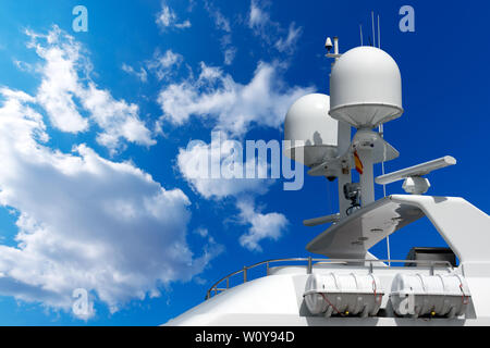 Detail of luxury white yacht with navigation equipment, radar, antennas and lifeboats on blue sky with clouds - Stock Photo